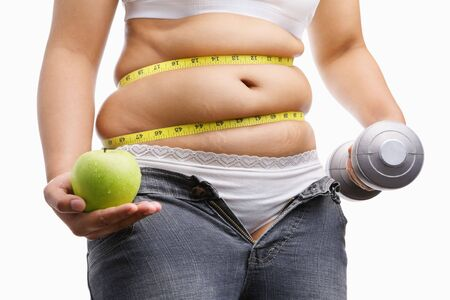 fat woman with unzup jeans holding apple and weight on each hand, id a concept to fight against obesity photo