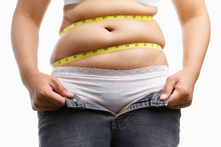 bellies: fat woman holding her unzip jeans with measuring tape around her belly, a concept to get a diet