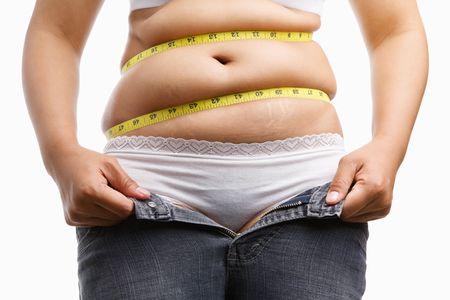 pancia grassa: FAT woman holding lei decomprimere jeans con nastro intorno la sua pancia, un concetto per ottenere una dieta di misurazione