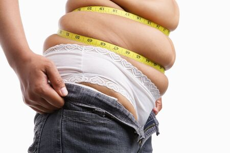 Fat woman trying to wear tight jeans from side with measuring tape around her belly photo