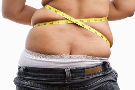 Back side of fat woman with measuring tape, a concept to get a diet photo