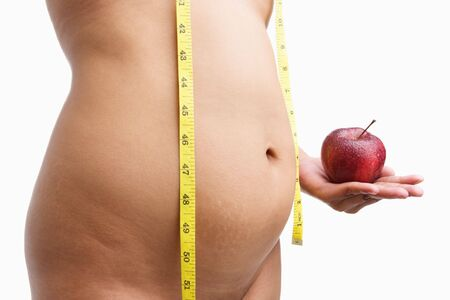 Overweight woman body holding apple with measuring tape, a concept to have healthy eating. photo