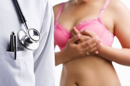 Doctor and woman on pink bra holding her breast, a concetp for breast cancer examination