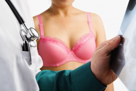 Doctor examine xray slide with woman on pink bra waiting on background Stock Photo