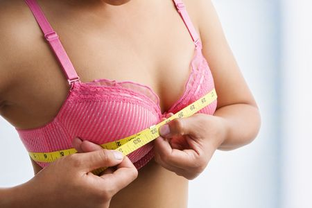 Woman measuring breast size with yellow measuring tape on room. photo