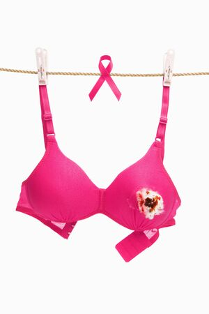 Broken pink bra for breast cancer concept with ribbon, shot over white background Stock Photo