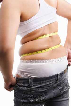 Fat woman trying to wear tight jeans from backside with measuring tape around her belly photo