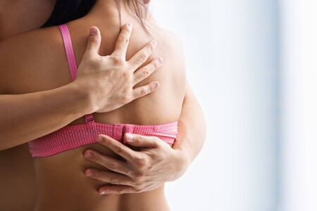 Hand supporting breast cancer victim, on the back of woman using bra with one strap only photo