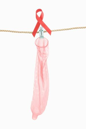 Condom hanging with red ribbon over white background, a concept for AIDS prevention photo