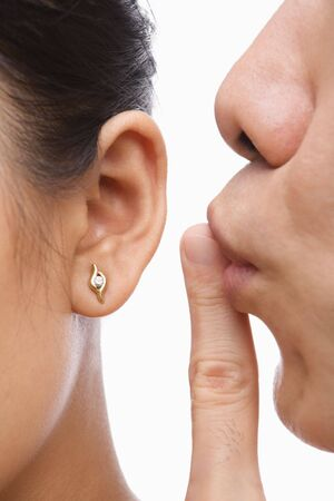 man shhing woman on her ear over white background. photo