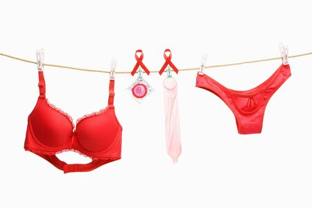 red condom: Red underwears, ribbon for AIDS cause and condoms hanging on rope, shot over white background Stock Photo