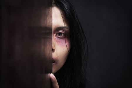 Injured woman hiding in dark, concept for domestic violence photo