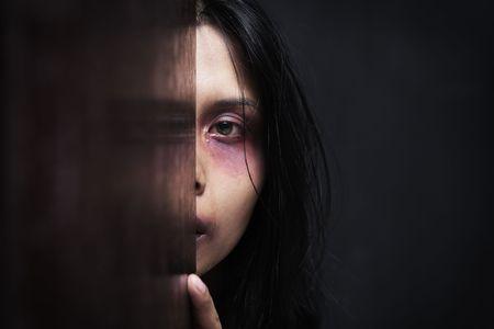 violencia intrafamiliar: Mujer lesionada escondida en la oscuridad, el concepto de violencia en el hogar  Foto de archivo