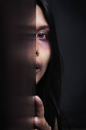 violencia intrafamiliar: Mujer herida escondida en la oscuridad, el concepto de violencia dom�stica Foto de archivo