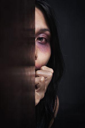 violencia: Mujer lesionada escondida en la oscuridad, el concepto de violencia en el hogar  Foto de archivo
