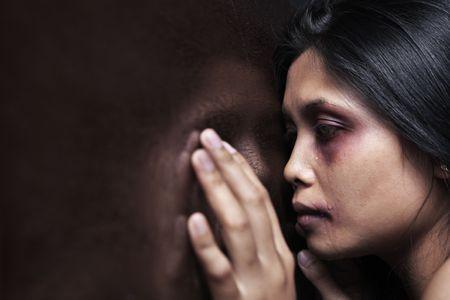 violencia intrafamiliar: Mujer herida apoy�ndose lamentablemente en la pared de madera, concepto para la violencia dom�stica Foto de archivo
