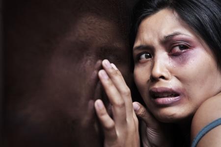 violencia intrafamiliar: Mujer herida aterrorizada, apoy�ndose en la pared de madera. Concepto de violencia dom�stica Foto de archivo