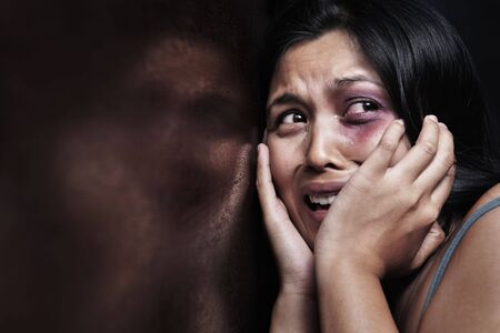 horrified: Injured woman terrified, leaning on the wooden wall. Concept for domestic violence