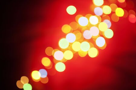 Blurred christmas lamp arranged diagonally on red background photo