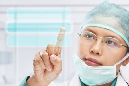 female medical worker or reseacher or scientist touching virtual button panel photo