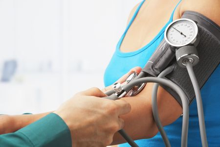 body check: Checking blood pressure of female patient, unrecognizable people Stock Photo