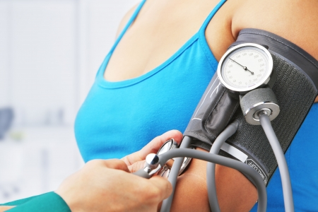 blood pressure: Checking blood pressure of female patient, unrecognizable people Stock Photo