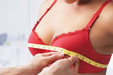 adult breast: Measuring bust size of woman wearing red bra