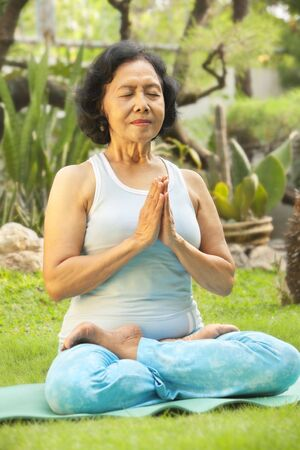 Asian senior woman meditating for yoga outside, green plant as background photo