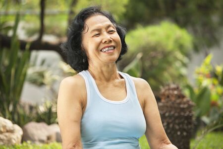 Senior Asian woman laught at park after yoga training photo