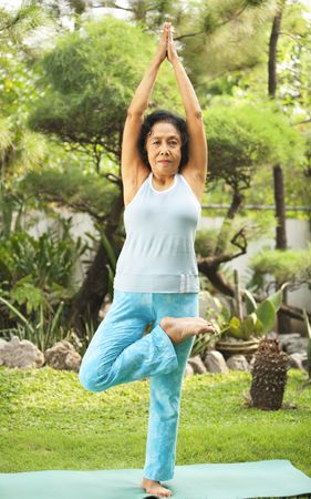 ps: Senior Asian woman doing yoga at park in the morning. PS: stitching the image at the upper part