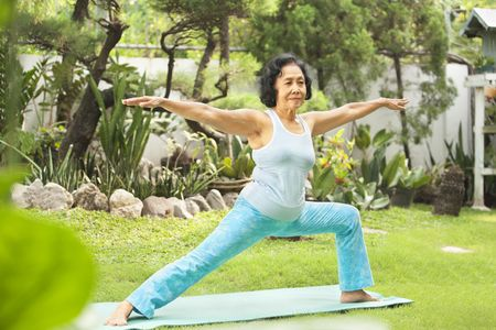 warm up exercise: Senior Asian woman doing yoga at park in the morning Stock Photo