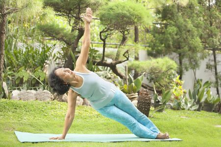 Senior Asian woman doing strecthing for yoga in garden photo