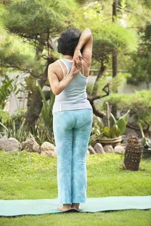 Senior Asian woman doing strecthing for yoga in garden Stock Photo - 6264372