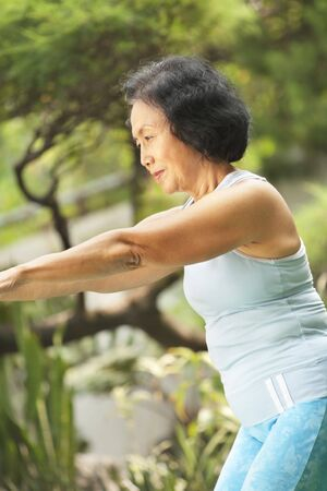 Senior old Asian woman doing yoga in park alone photo