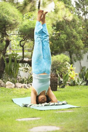 headstand: Senior Asian woman doing Yoga practice at garden in the morning