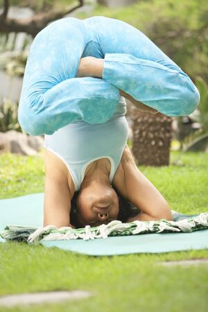 Senior Asian woman doing Yoga practice at garden in the morning photo