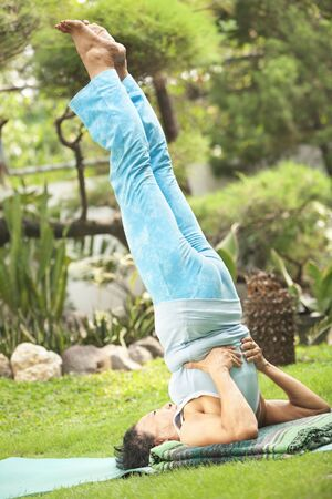 Flexible senior woman doing yoga outside in garden photo
