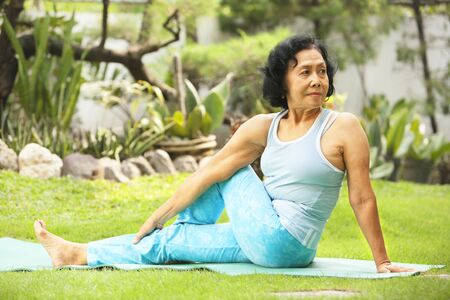 headstand: Asian senior old woman practicing yoga at garden Stock Photo