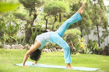 Asian senior old woman practicing yoga at garden photo