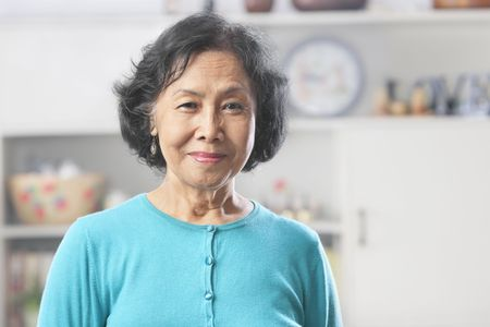 old people smiling: Senior Asian woman at home gazing to camera Stock Photo