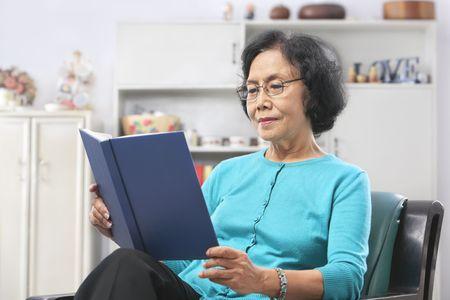 mujer leyendo libro: Senior mujer asi�tica que leer el libro en casa