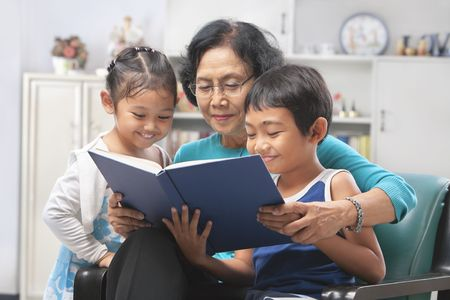 Grandma and grandchildren reading book together at home Stock Photo - 6264306