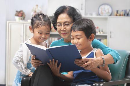 mujer leyendo libro: La abuela y nietos leyendo el libro juntos en casa  Foto de archivo