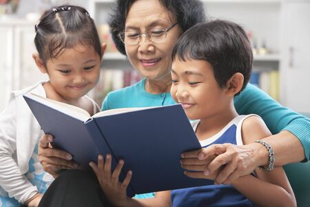 Grandma and grandchildren reading book together at home photo