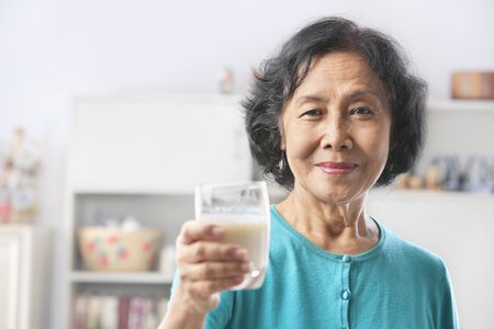 health drink: Senior woman holding glass of milk, offerng to camera. PS: shallow depth of field