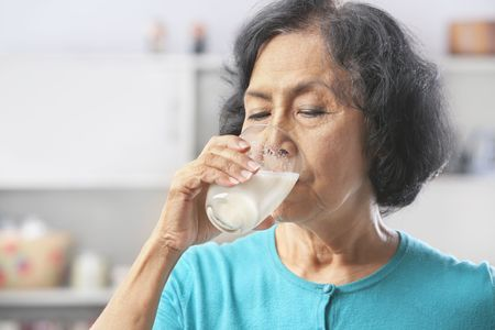 glass of milk: Senior Asian woman drinking milk at home