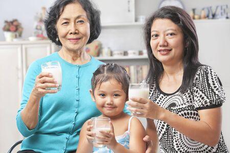 three generations: Three Asian female generation holding a glass of milk