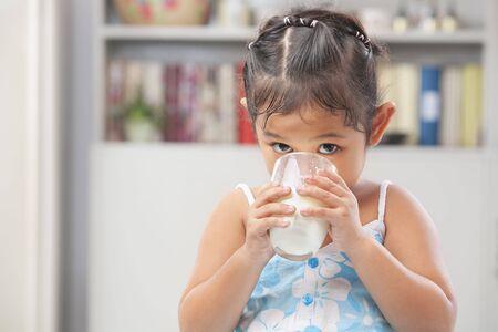 Little Asian girl drinking a glass of milk photo
