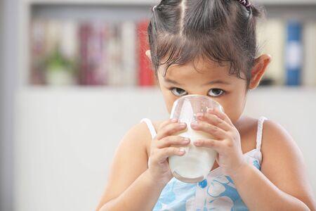 Little Asian girl enjoy drinking a glass of milk photo