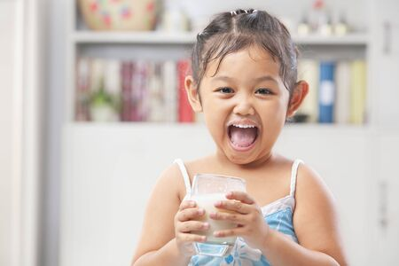 Little Asian girl look so happy after drinking milk photo